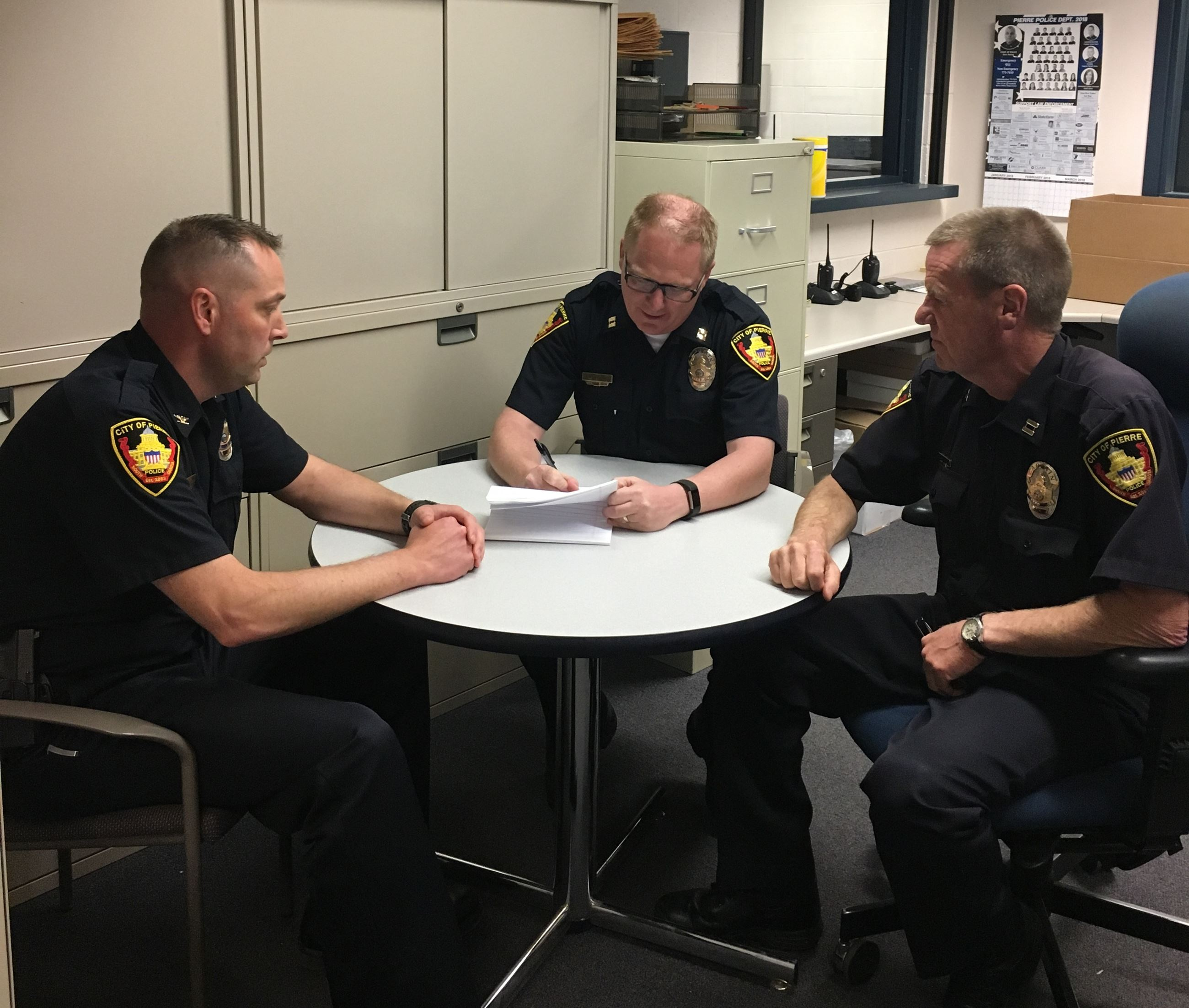 Police officers sitting around a table looking at paperwork