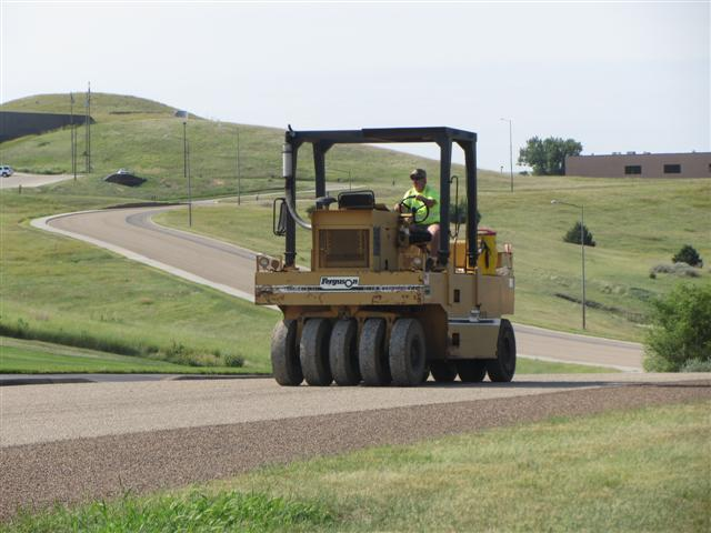 Crews chip seal Governors Drive. The roller sets the rocks, called chips, into a thin layer of aspha