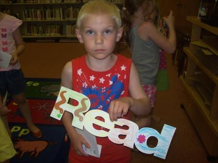 Child Holding  a Read Sign