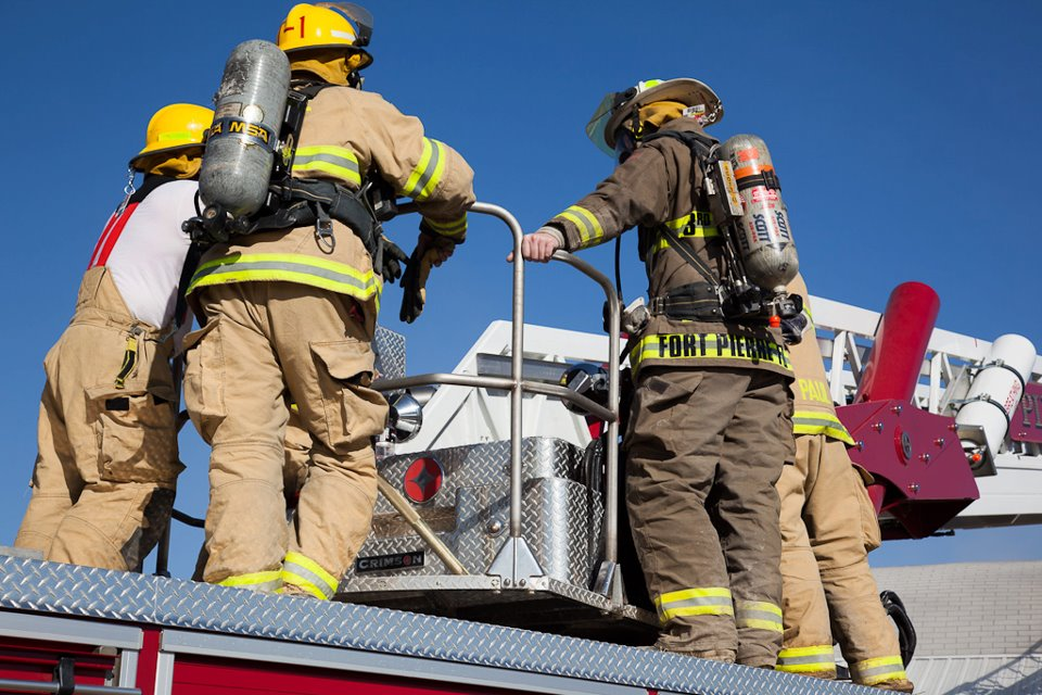 Firefighers on top of fire engine